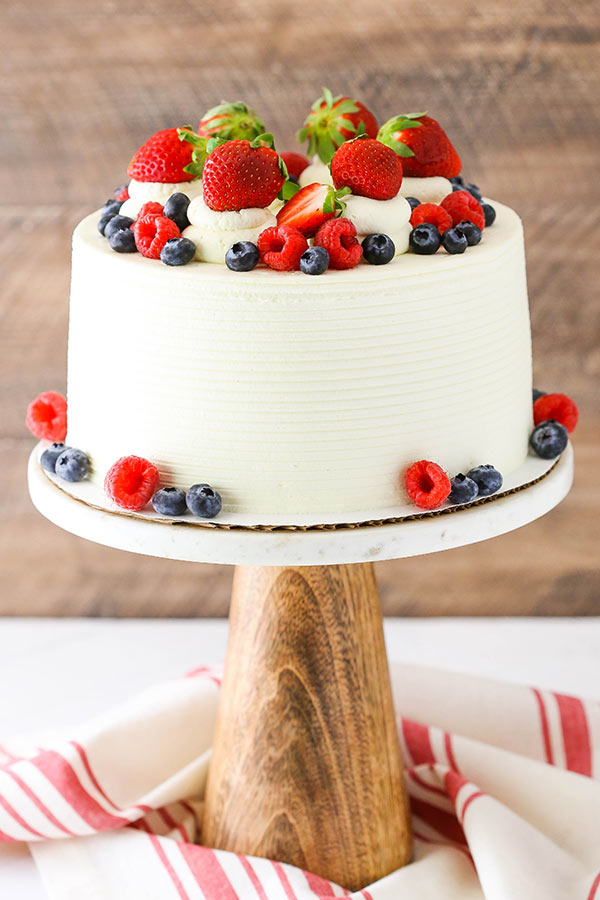 Berry Mascarpone Layer Cake - This Berry Mascarpone Layer Cake has layers of fluffy vanilla cake, fresh berry filling and mascarpone whipped cream frosting! It's light, fruity and perfect for spring!