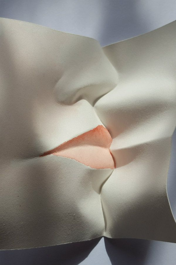 watercolor paper sculpture of two faces kissing, one with colored lips