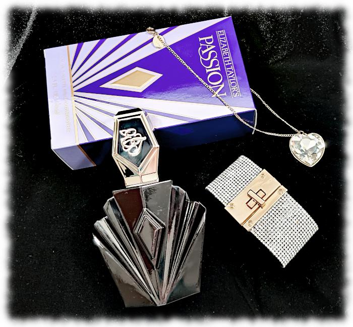 Flatlay of Passion bottle, box, heart-shaped necklace & diamante bracelet