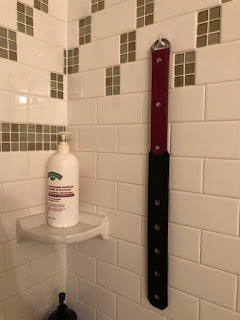 leather strap in the bathroom belonging to Professional Disciplinarian