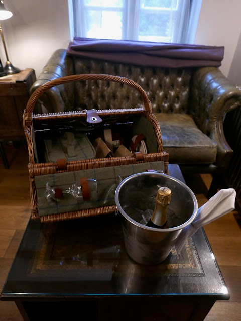 A round wicker hamper open to reveal glasses and brown paper bags of food, next to half a bottle of champagne in an ice bucket.
