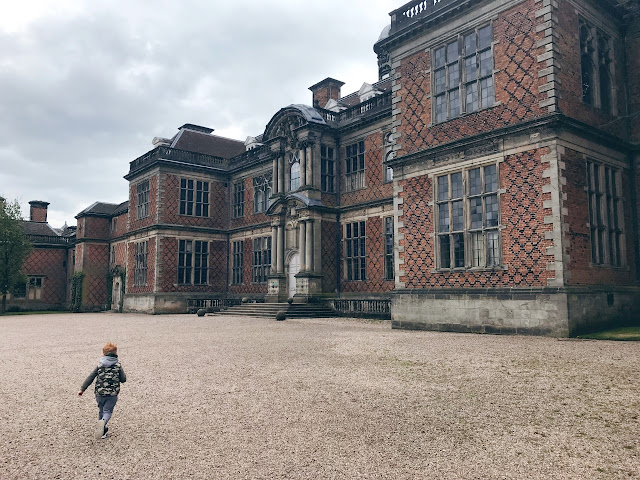 Child running in front of a country house