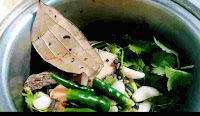 Fresh cilantro leaves, green chili, bay leaf and other spices in a mixing jar to make chicken cafreal recipe masala