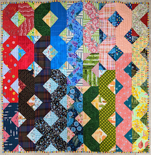 The hatchet block forms ribbons of color down the surface of this small quilt.