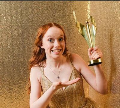 Amybeth McNultyholding the award