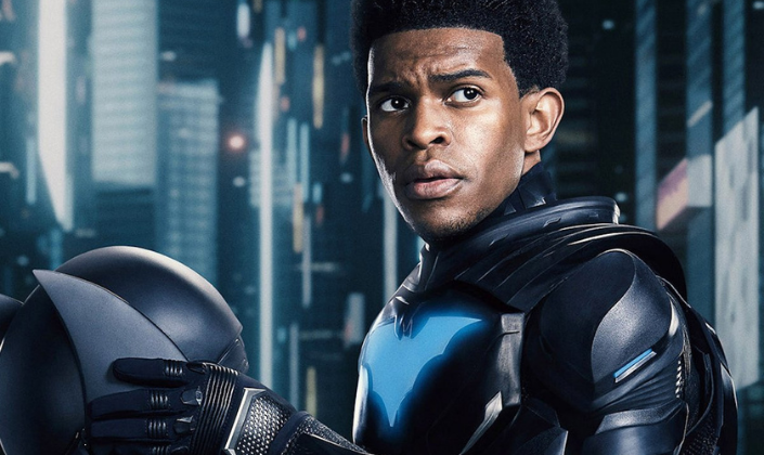 Imagem: a imagem promocional do personagem Luke Fox, um homem negro de cabelos pretos num penteado afro e olhos castanho-escuros com sobrancelhas grossas, num traje tecnológico de morcego, com luvas de couro, segurando um capacete de morcego.