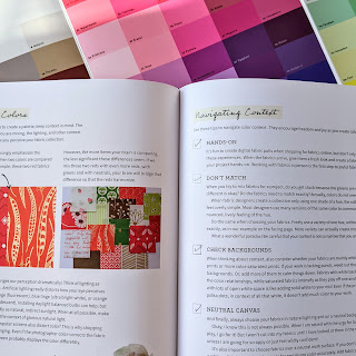 The Quilter's Frield Guide to Color book open with color swatches in the background