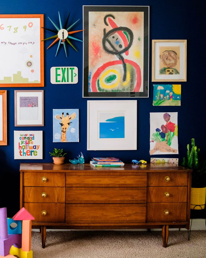 Gallery wall on blue wall w/mid century dresser