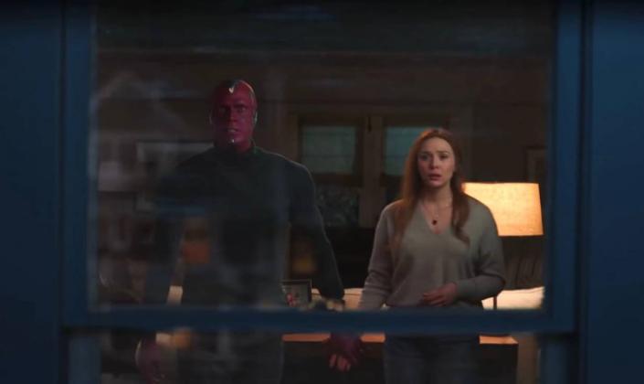 Imagem de capa: o Visão e Wanda, ambos em roupas caseiras, de mãos dadas olhando através da janela um brilho avermelhado do domo de energia estática se aproximando.