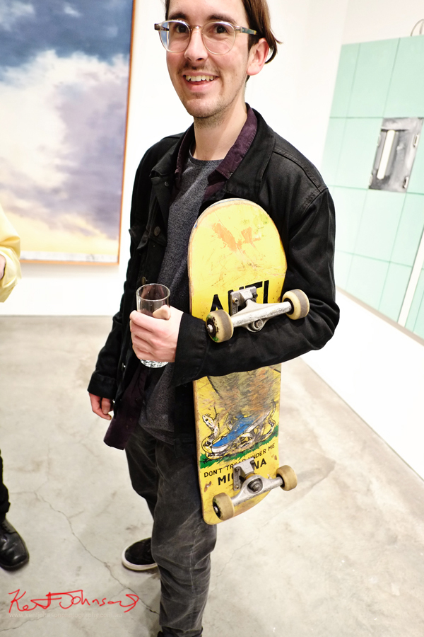 Skater with deck drinking water at an art opening. Street Fashion Sydney by Kent Johnson.