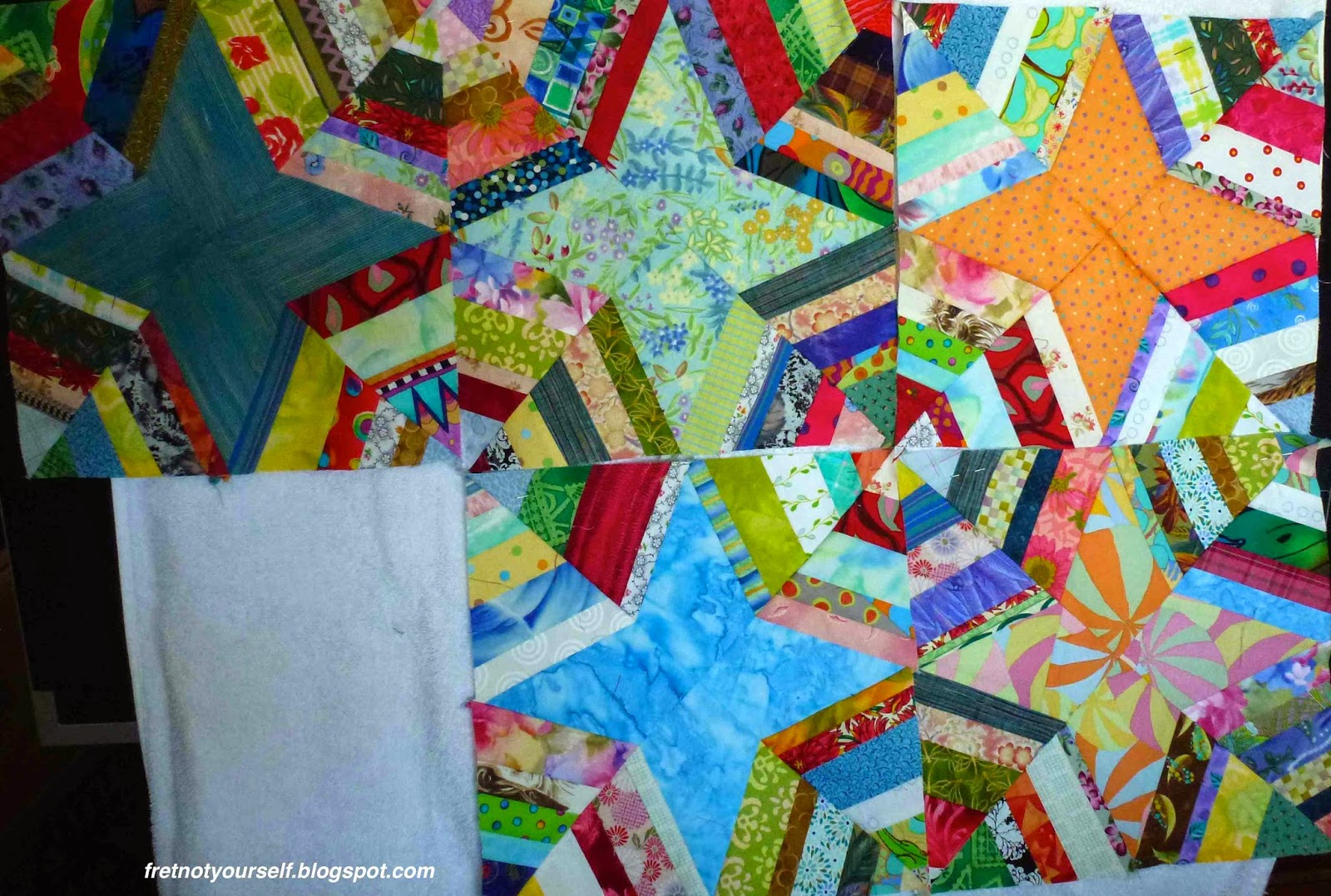 Spiderweb quilt blocks made of strings on blue, green, orange background stars.