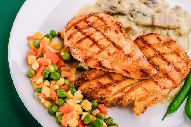 Pechugas de pollo a la parrilla con ensalada de zanahoria, granos de elote y chícharos