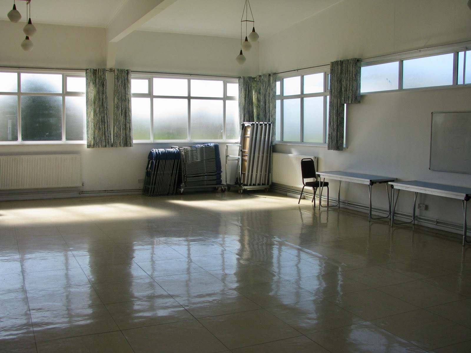 Large space, linoleum floor, Windows letting in sun light, folding chairs stacked. Radiators fitted to walls.
