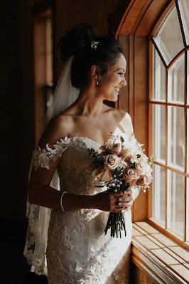 Novia luciendo joyas mirando por la ventana y llevando un ramo en la mano