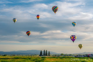 Cramer Imaging's fine art photograph of a hot air balloon cluster taking flight over a field in Panguitch Utah with a blue partly cloudy sky