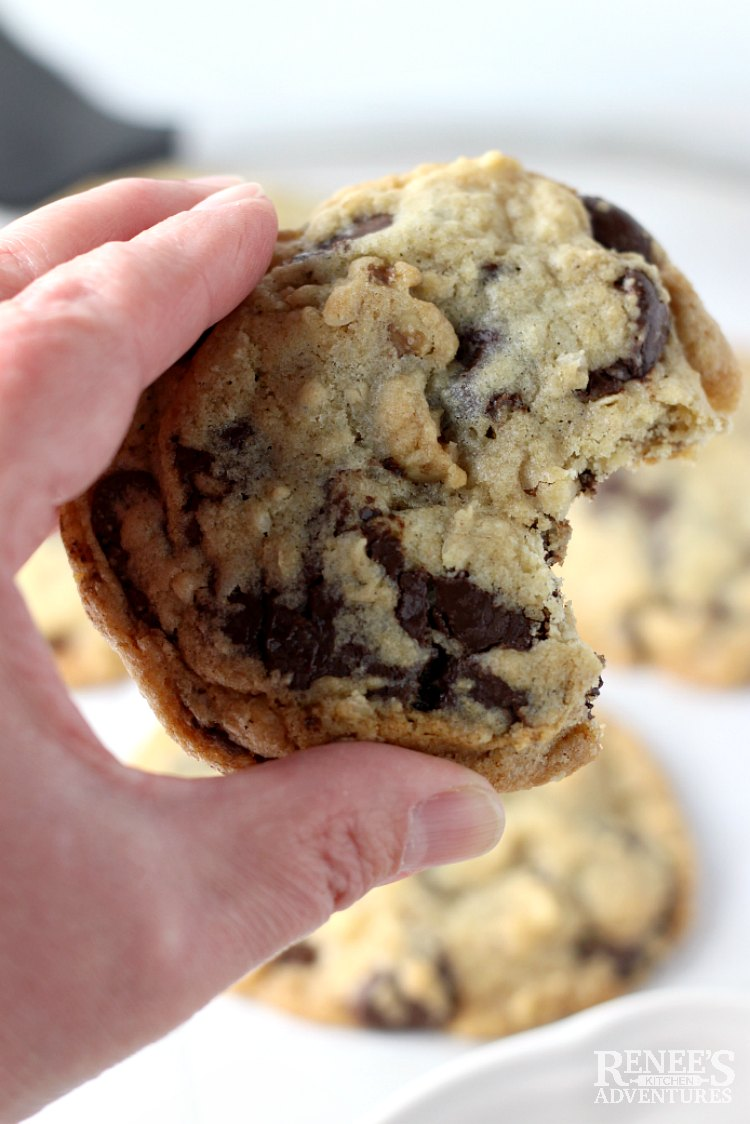 Close up of DoubleTree Chocolate Chip Cookie with a bite taken out being held by a hand