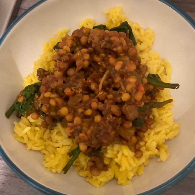A bowl of lamb and lentil curry with rice and spinach
