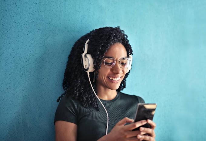 Mulher com headphone branco olhando para um celular preto na mão. Ela está escorada em um muro azul celeste.
