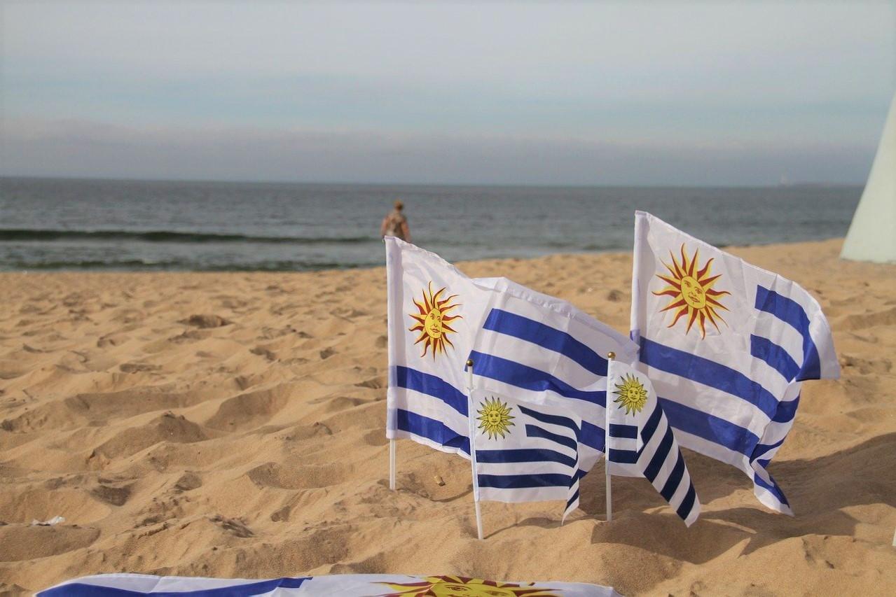 areia ade praia com 3 bandeirinhas do uruguai