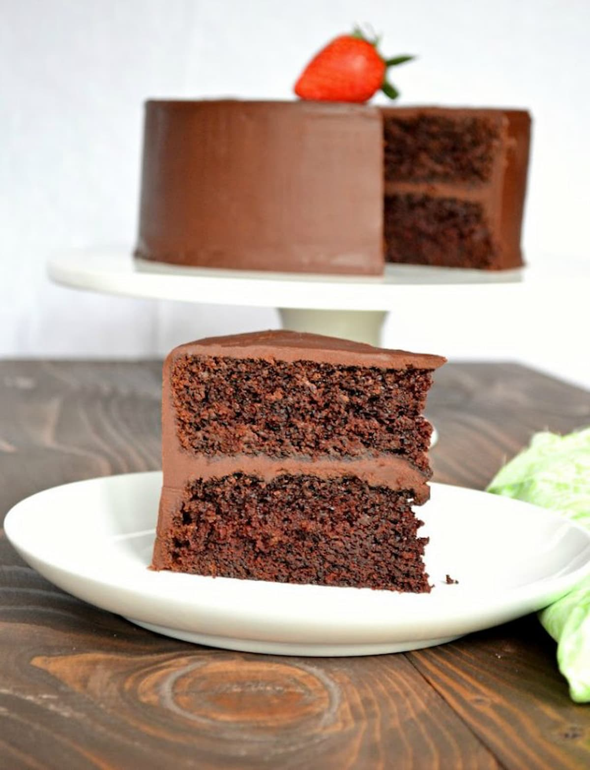 A slice of Chocolate Cake with Ganache Frosting on a white plate with the whole cake in the background on a white cake stand.