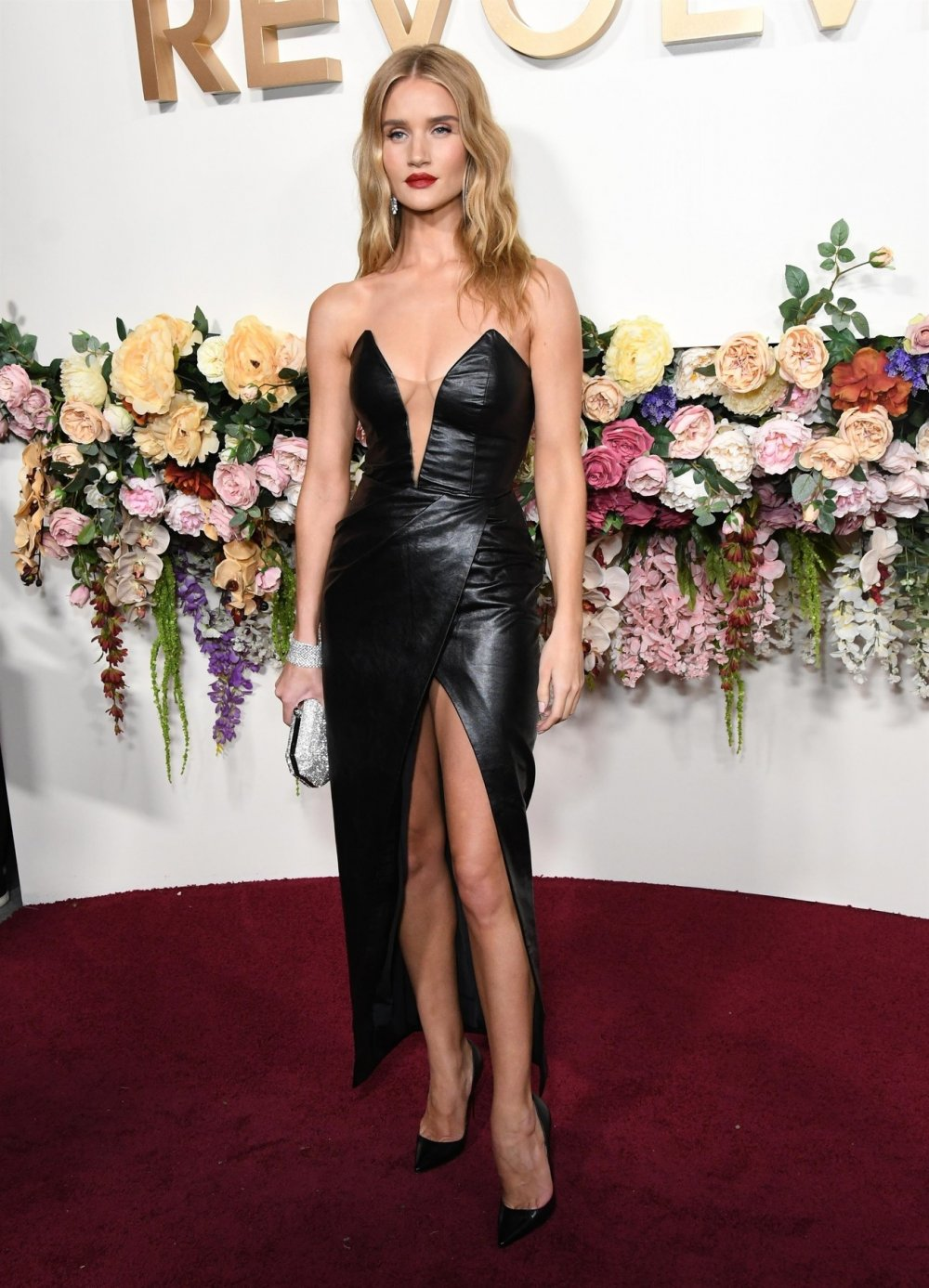 Rosie Huntington-Whiteley sets pulses racing in a perilously plunging black PVC wrap dress as she leads the stars at the Revolve Awards in LA