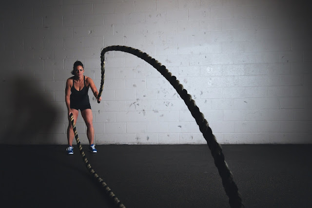 Woman Exercising at Gym with Battle Ropes