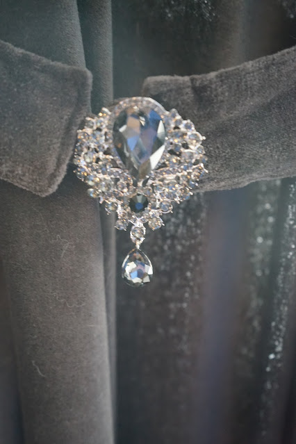 Large brooch on curtain tie back