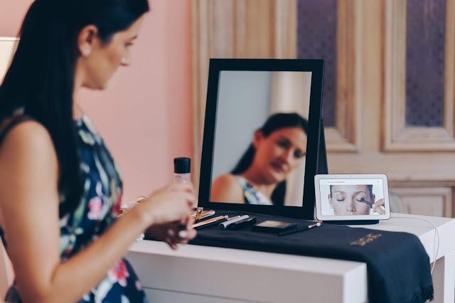 Eine Frau vor einem Spiegel, die über den Google Nest Hub ein Tutorial schaut