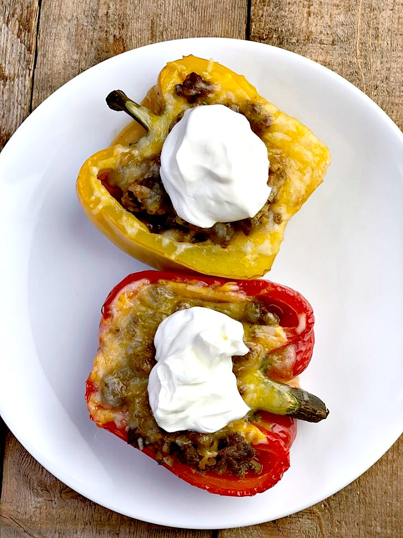 Low Carb Taco Stuffed Peppers - This Taco Stuffed Pepper recipe is a game-changer for a low carb lifestyle! Oven-roasted bell peppers packed with taco seasoned ground beef and topped with gooey melted cheese. This delicious alternative to tacos removes the tortillas and allows you to enjoy Taco Tuesday without all the added carbs or guilt. #lowcarb #keto #taco #peppers #stuffedpeppers #Mexican #recipe #5ingredients | bobbiskozykitchen.com