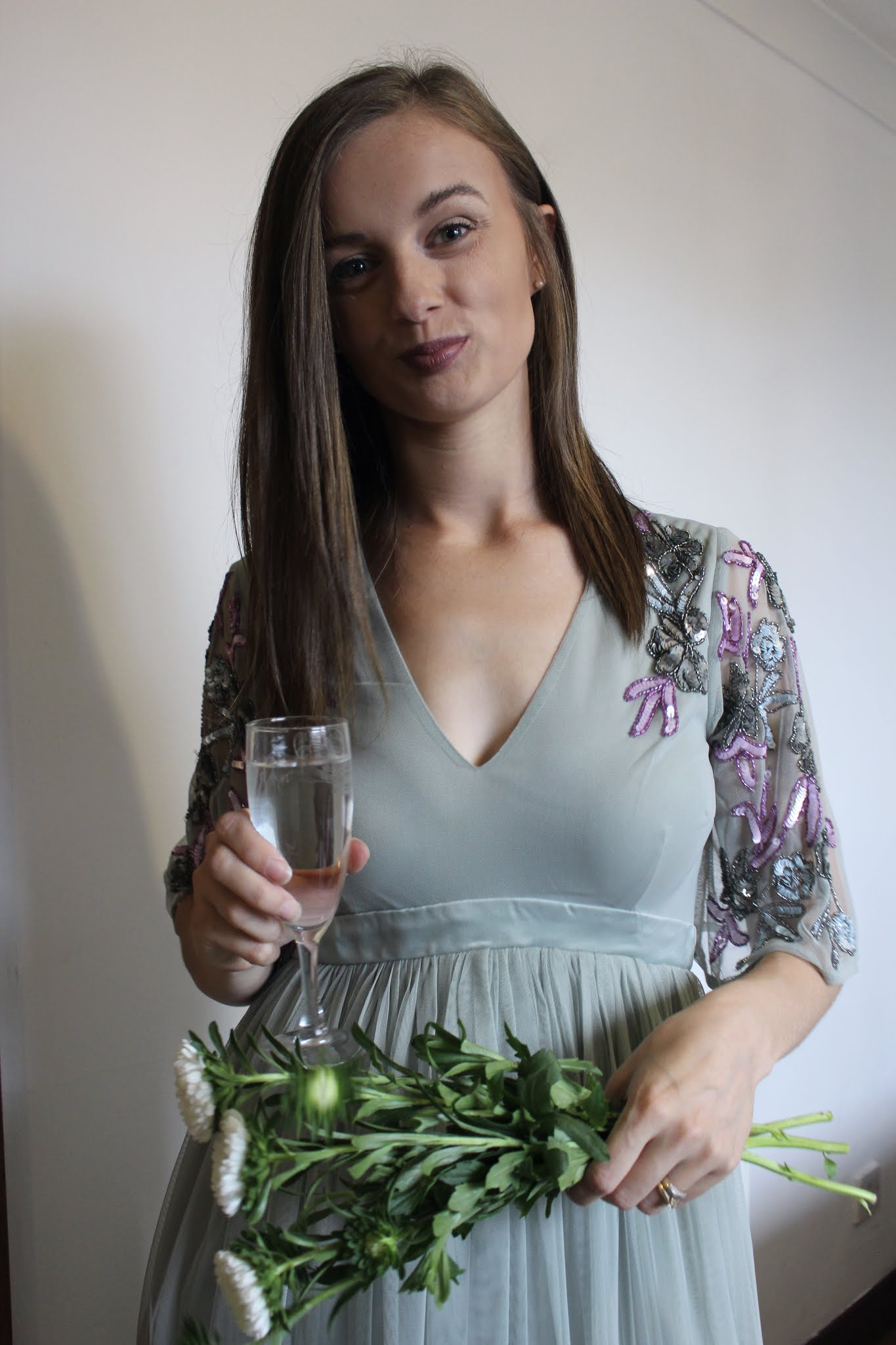 Why turning 30 isn't that bad after all. Claire smiling at the camera holding a bunch of flowers and a champagne flute cheersing to turning 30.