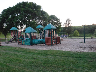 a brown and green play structure at Bacon Creek Park