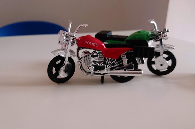 Two toy motor bikes standing on a white table facing opposite directions. The fore front motor cycle is red with silver motor and features, the other in the back has a green and silver scheme. In the background has the top of a blue chair with light cream wall.