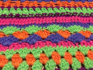 A close up of Sarah's multistitch blanket. It is worked in very bright 'zingy' colours: green, orange, pink, purple and blue.