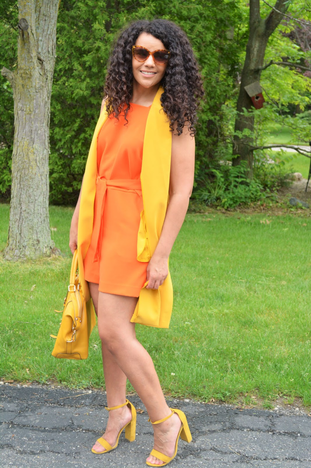 Over 40 fashion blogger Mary of Curlybyrdie Chirps in a yellow vest and orange romper suit