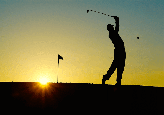 Silhouette of a golfer swinging in the sunset