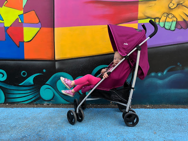 A side view of the purple umbrella fold pushchair against a bright gravity wall with a toddler peering out