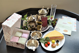 Betty's cafe tea rooms play resources set up on a tuff spot tray with fondant fancies silverware and sandwiches
