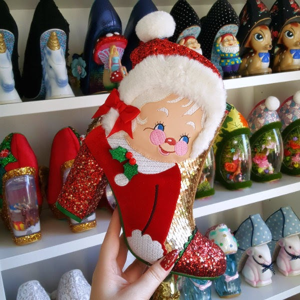 hand holding red and gold festive themed ankle boot with Mrs Claus applique face with shoe shelves in background