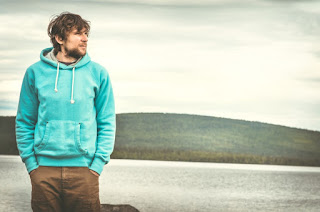 man wearing a hoodie near a lake