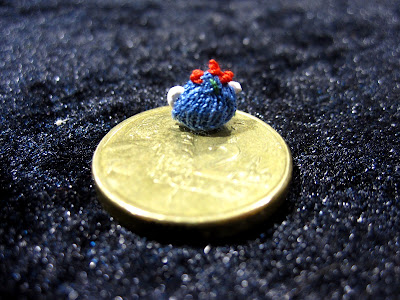 Tiny hand-knitted tea cosy displayed on an AU $2coin