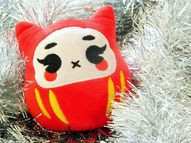A photo showing a plushie of a traditional japanese new year mascot. it is red and yellow, and is sitting on silver tinsel.