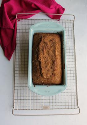 loaf of cinnamon bread in pan on cooling rack
