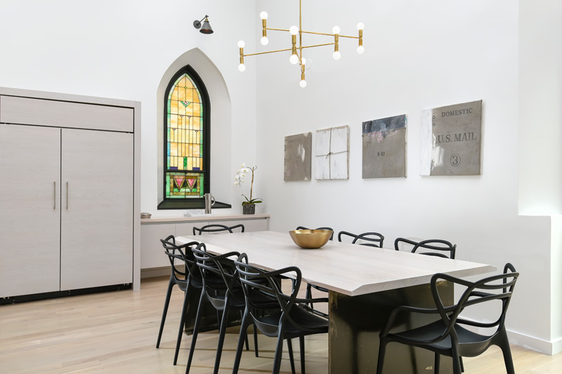 Modern dining room with stained glass window in Church conversion to home in Chicago