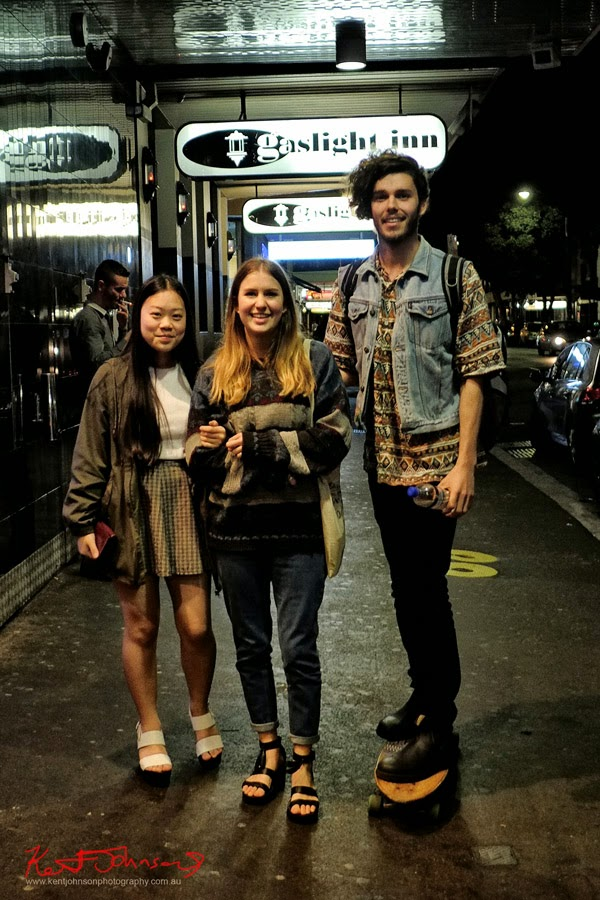 Portrait of three out in Sydney on a winter night, open toe shoes, short skirt, him, jeans boots tee shirt with denim jacket no sleeves. Photo by Kent Johnson.