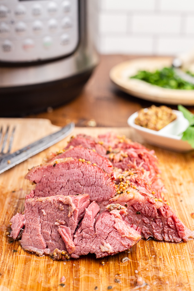 Closeup photo of the cooked Keto Corned Beef sliced on a wooden cutting board.