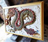 Relief gambar naga dibuat dari batu alam paras jogja atau batu alam paras putih