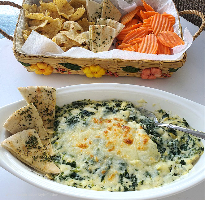 this is a recipe for baked artichoke and spinach dip with all kinds of crackers, breads and vegetables to dip into this cheesy baked dip