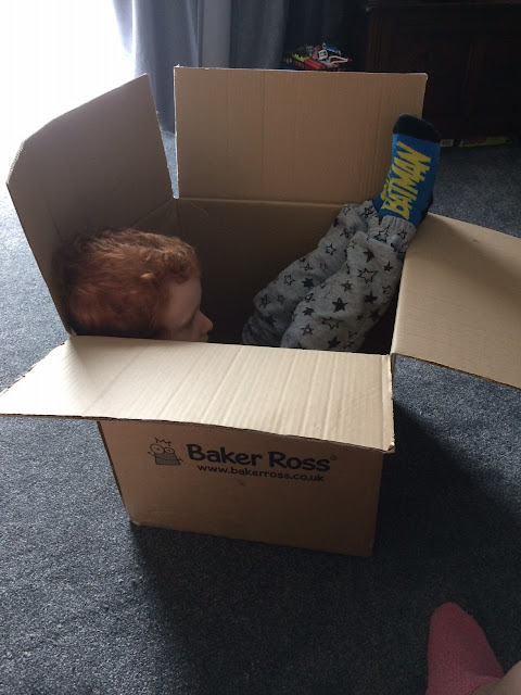A child sitting in a box watching television