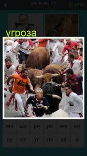 на улице люди разбегаются от быков, так как они представляют угрозу для них