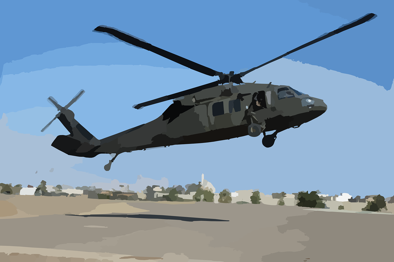 a black hawk helicopter hovers low above the ground to illustrate a blog post about remembering the battle of mogadishu